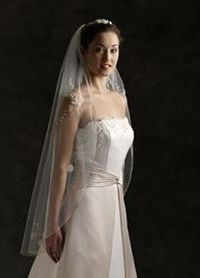 This elegant one-tier veil features a metallic pencil edge and delicate lace embroidered flowers. The fingertip length measures approximately 40 inches long. Wire comb. Available in White or Ivory. Imported.