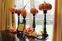 Spray-paint candlesticks black and top with pumpkins for an elegant Halloween centerpiece or tabletop decoration.